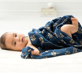 Baby in Aden and Anais muslin swaddle blanket